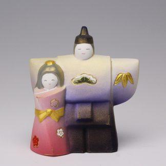 緒方恵子の博多人形「おひなさま」です。紫色の着物を着たお内裏様と桃色の着物を着たお雛様が幸せそうに並んでいます。