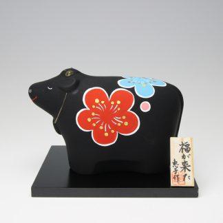 緒方恵子の博多人形「福が来た(干支・丑)」です。黒い牛の横と背中に赤色と水色の梅の花が描かれています。