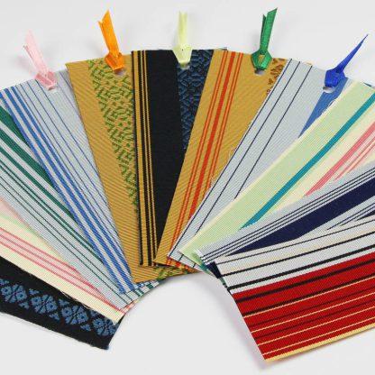 宮嶋美紀の博多織で作られたしおりです。11種類の色とりどりのしおりが扇状に並べられています。