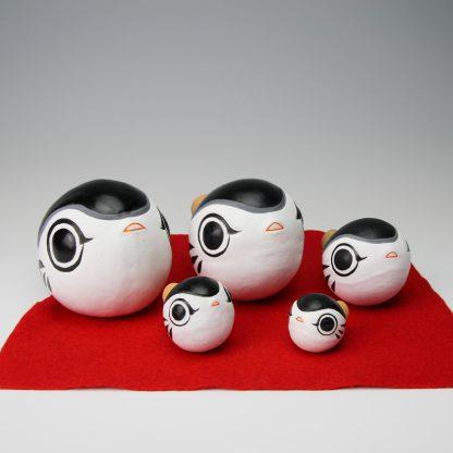 垣内敬一人形の作品「ふく笛」です。大きさが、特大、大、中、小、ミニの5つのふく笛が赤い毛氈の上に並べられています。