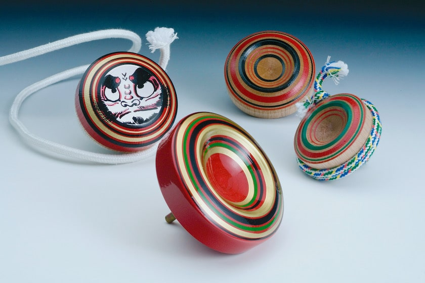 博多の伝統工芸品である博多独楽です。大小、4つの赤、緑、紺、金の色からなる博多独楽が並んでいます。