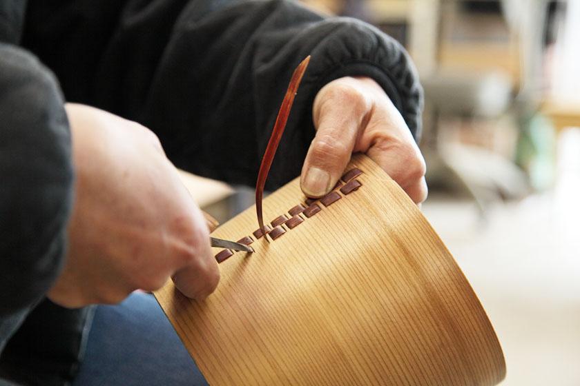 博多曲物の飯櫃を作っています。杉の木を円形に丸め、桜の皮でつなぎ目を縫い合わせています。