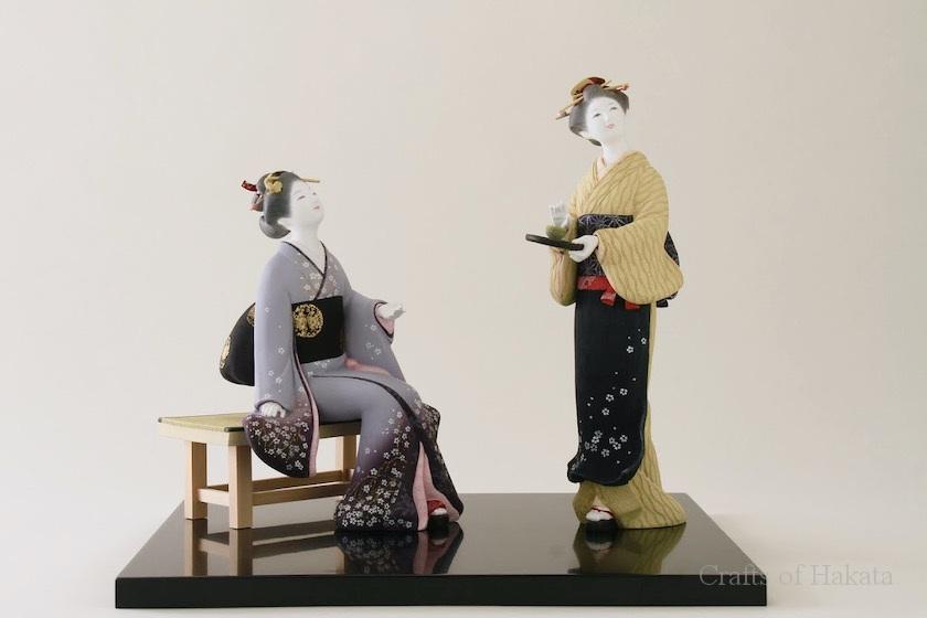 緒方恵子の博多人形の作品「桜舞う」です。着物を着た二人の女性の博多人形です。椅子に腰掛けた女性と茶碗を乗せたお盆を持って立っている女性が遠くを見ています。