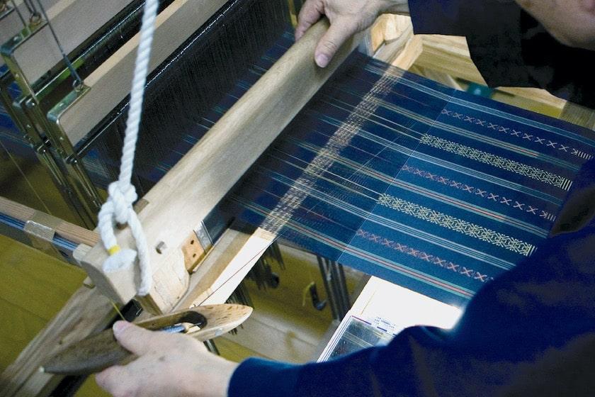博多織を織り機を使って織っているところです。縦糸と横糸を交差させて織っています。