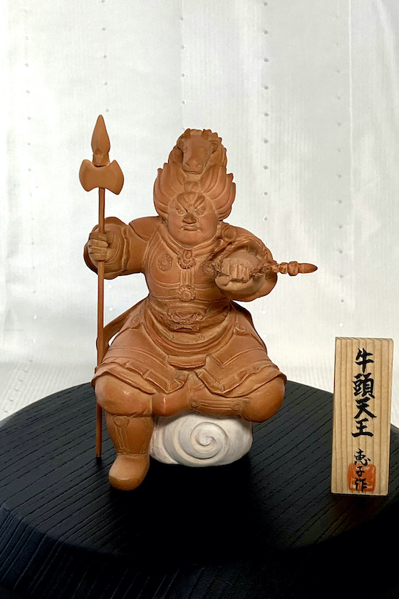 緒方恵子の博多人形の作品「牛頭天王」です。牛頭天王は、インドの祇園精舎の守護神、素戔嗚尊の化身です。魔除けの神、疫病よけの神として、祇園祭で祀られます。牛頭を頭につけ、右手に羂索、左手におのを持ち右膝を立てて座っています。