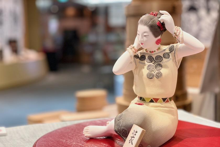 緒方恵子の博多人形の作品「装」です。座っている女性が髪に赤い櫛をつけています。
